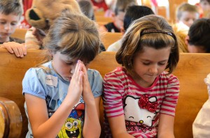 Children praying during a time of worship at Vacation Bible School in 2013.